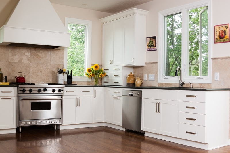 A white kitchen with a cooktop and wall oven.