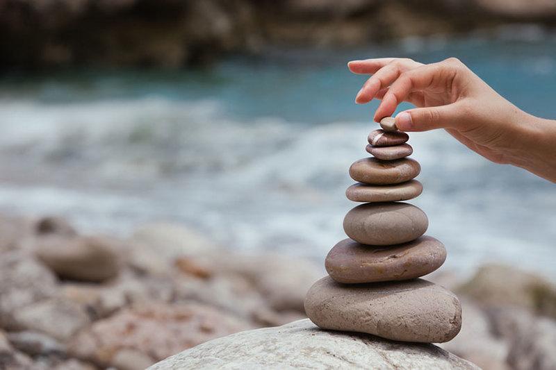 Hands stacking rocks