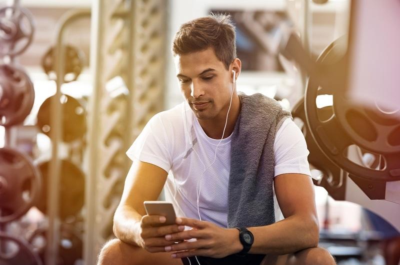 Man listening to headphones in gym