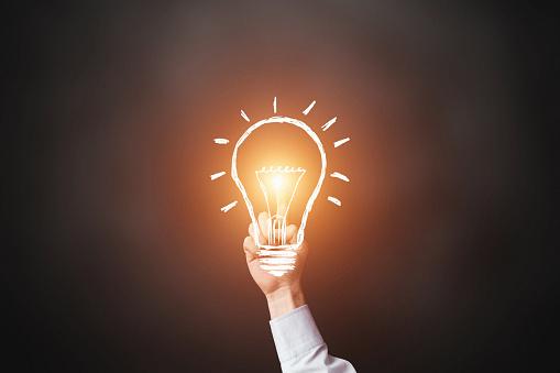 A hand holding a lit light bulb.