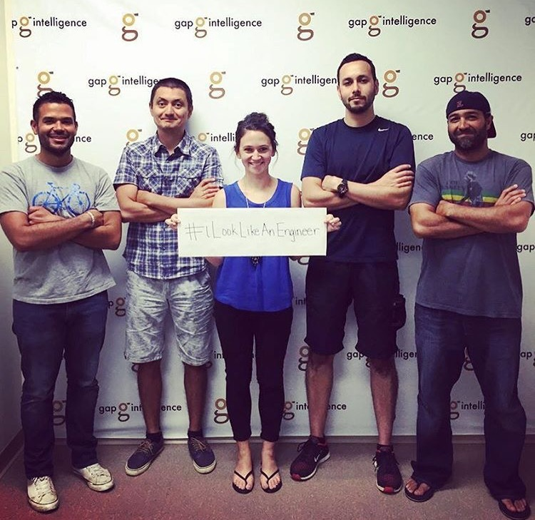 The dev team with Caitlin holding a sign that says #ILookLikeAnEngineer.