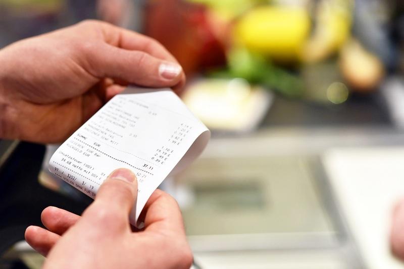 Hand holding a receipt.